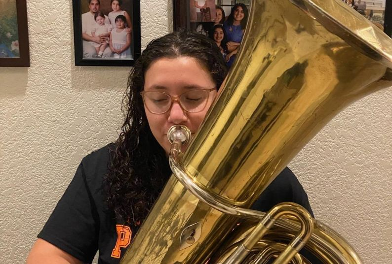 Jolene Villavicencio at home with the tuba the Conservatory of Music loaned her.