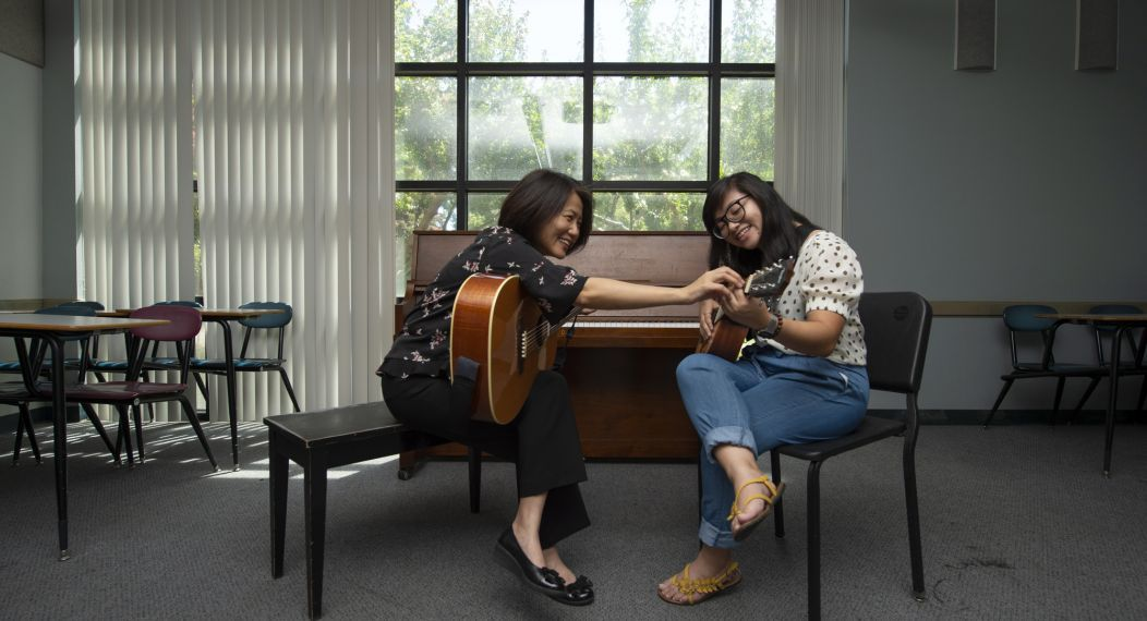 music therapy lesson on the guitar between student and faculty