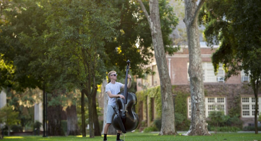 Michael Andersen practices his bass on Knoles Lawn 2019